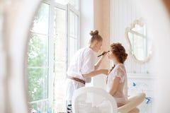 美发师在婚礼前做构成新娘 免版税库存照片