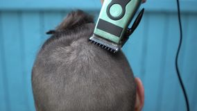 美发师在客户的项的裁减头发有电剃刀飞剪机和梳理视图关闭的 股票视频