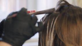 美发师在秀丽演播室,妇女做头发染色改变她的神色、专业着色和护发,秀丽 影视素材