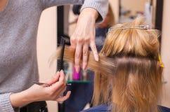 美发师对与头发剪刀的理发做一个女孩,金发碧眼的女人 免版税库存照片