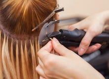 美发师对头发引伸做一个女孩,美容院的一个金发碧眼的女人 免版税库存图片