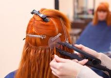 美发师对头发引伸做一个年轻,红发女孩,美容院的 免版税库存照片