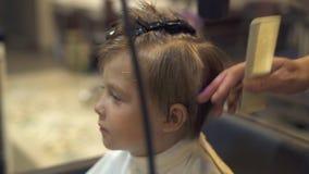美发师小男孩的干毛发,当切开在理发沙龙时的孩子 理发师吹的孩子的关闭 影视素材