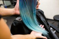 美发师展示他的与美丽的女孩的工作 理发师理发被洗染的头发颜色蓝色 免版税库存照片
