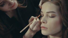 美发师投入一双黑眼睛遮蔽一个深色的模型的眼皮 股票录像