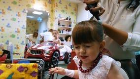 美发师梳头发用一个逗人喜爱的女孩的发摩丝 股票录像