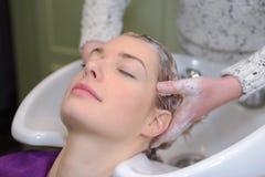 美发师洗涤的头发客户 图库摄影
