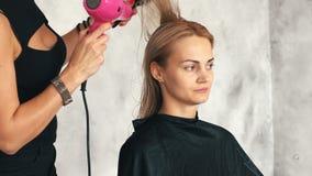 美发师烘干一个年轻白肤金发的女孩的吹风机头发 股票视频