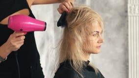 美发师烘干一个年轻白肤金发的女孩的吹风机头发 影视素材