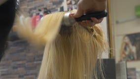美发师理发师梳她的头发给使用hairdryer的一名白肤金发的妇女 影视素材