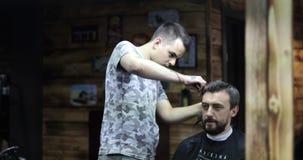 美发师用运转与顾客的被刺字的手 股票录像