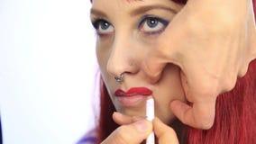 美发师画式样` s嘴唇的等高有一支红色铅笔的 化妆师应用有刷子的唇膏在妇女的 影视素材