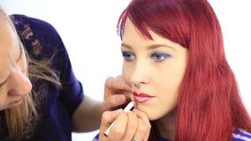 美发师画式样` s嘴唇的等高有一支红色铅笔的 化妆师应用有刷子的唇膏在妇女的 股票录像