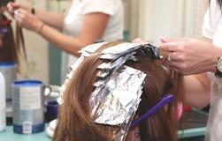 美发师着色头发在演播室 免版税图库摄影