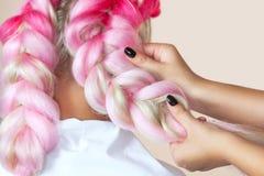 美发师编织与桃红色kanekalons美丽的金发碧眼的女人的辫子 库存图片