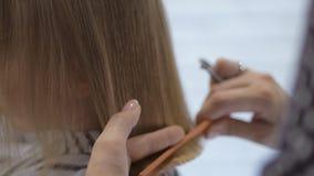 美发师美发师做一逗人喜爱的女孩的一种发型发廊的 理发,头发切口 股票视频