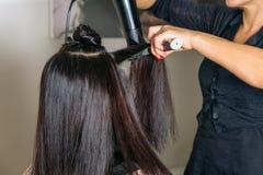 美发师递有打击烘干机和圆的刷子的干燥长的黑发 式样` s面孔用头发盖 免版税库存照片