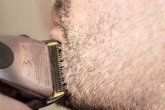 美发师,切开胡子在她的工作地点 库存图片