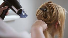 美发师,当切开干毛发客户时 做理发的美发师特写镜头对有剪刀的妇女在美发店 股票录像