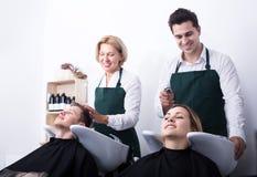 美发师洗涤客户的头发 免版税图库摄影