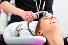 美发师洗涤的头发的妇女 免版税库存照片