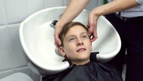 美发师洗男孩的头发美容院的 股票视频