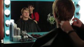 美发师`的s一个人 准备一个人的女性理发师对有头发裁减 股票录像
