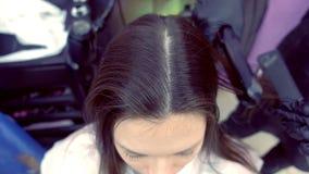 美发师straights使用头发钳子的美女的黑褐色头发在发廊 股票录像