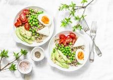 美味早餐五谷碗 平衡的菩萨碗用奎奴亚藜,鸡蛋,鲕梨,蕃茄,在轻的背景的绿豆 健康的饮食 免版税库存照片