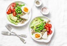 美味早餐五谷碗 平衡的菩萨碗用奎奴亚藜,鸡蛋,鲕梨,蕃茄,在轻的背景的绿豆 健康的饮食 库存图片