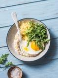 美味燕麦粥用煎蛋、芝麻菜和乳酪 可口健康早餐或午餐 在蓝色木背景 免版税库存图片