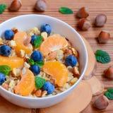 美味的燕麦粥粥用蜜桔、莓果、榛子和薄菏在一个白色碗 背景棕色木 免版税图库摄影