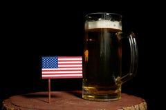 美国下垂与在黑色的啤酒杯 库存照片