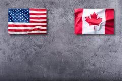 美国下垂和在具体背景的加拿大旗子 免版税库存照片