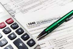 美国与笔和计算器的报税表1040 报税表法律文件 免版税库存图片