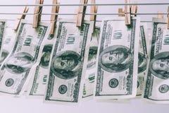 美国人一百元钞票在晒衣夹的烘干机垂悬 洗货币的清洁干燥欧元洗涤 库存照片