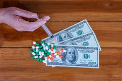 美国人与胶囊的拿着syr的一百元钞票和手 库存图片