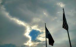 美国人和得克萨斯旗子与明亮的云彩 库存照片