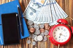 美国人在木背景的一百元钞票、硬币、电话、笔、笔记本和时钟特写镜头 时间是货币概念 图库摄影
