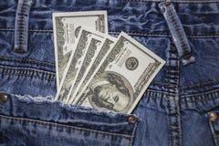 美国人在蓝色牛仔裤的后面口袋的100美金 图库摄影