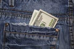 美国人在蓝色牛仔裤的后面口袋的100美金 免版税库存图片