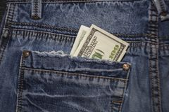 美国人在蓝色牛仔裤的后面口袋的100美金 库存照片