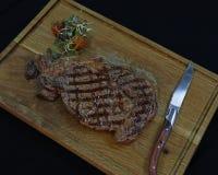 美国人安格斯牛肉烤了在木委员会的ribeye牛排有刀子的 库存照片