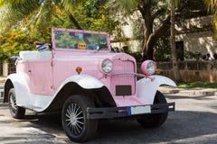 美国人玫瑰色福特敞篷车经典汽车停放了在巴拉德罗角古巴- Serie古巴报告文学的棕榈下 图库摄影