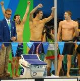 美国人的4x100m混合泳队Cory米勒(l),迈克尔・菲尔普斯和莱恩・墨菲庆祝胜利 免版税库存照片