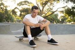 美国人30s坐冰鞋板在体育搭乘训练以后使用送互联网社会媒介tex的手机 图库摄影