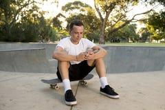 美国人30s坐冰鞋板在体育搭乘训练以后使用送互联网社会媒介tex的手机 免版税图库摄影