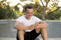 美国人30s坐冰鞋板在体育搭乘训练以后使用送互联网社会媒介tex的手机 免版税库存照片