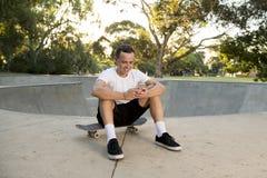 美国人30s坐冰鞋板在体育搭乘训练以后使用送互联网社会媒介tex的手机 库存图片