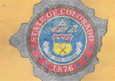 美国各州科罗拉多在具体孔和破裂的墙壁绘的封印旗子 库存照片